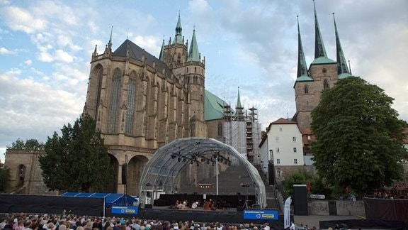 Blick auf den Dom mit einer Bühne und Besuchern.