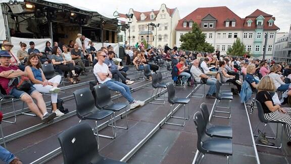 Besucher sitzen mit Abstand auf Stühlen.
