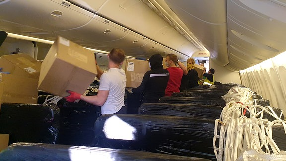 Männer stehen in der Kabine eines Passagierflugzeugs und entladen Kartons