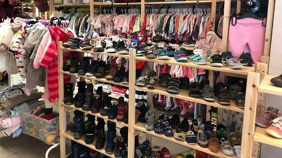 In einem Geschäft für Kindermode stehen Schuhe in Regalen und hängen Kindersachen auf Kleiderbügeln.