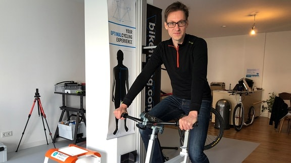 Sebastian Risse, sitzt auf einem Fahrrad, mit dem man Menschen vermessen kann.
