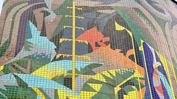 Wandmosaik mit Strommast und Dschungel.