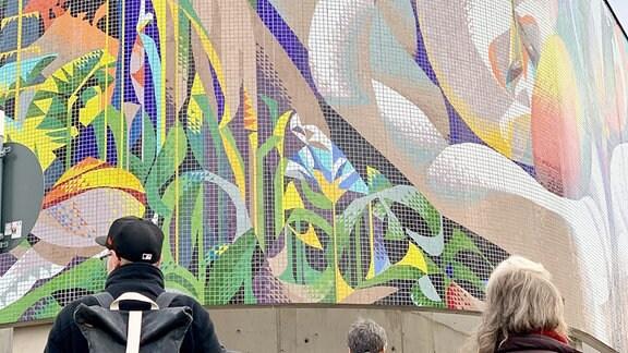 Menschen stehen vor abgerundeter Gebäudefassade mit Wandmosaik.