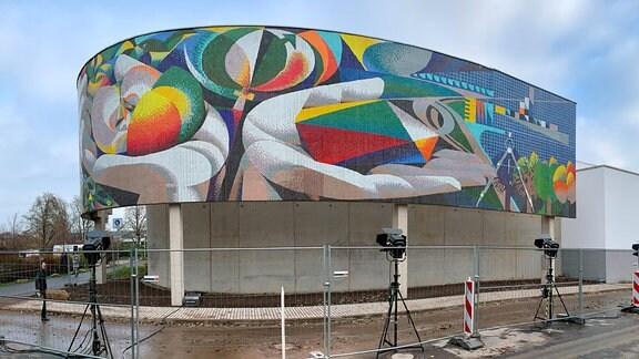 Gebäude mit abgerundeter Fassade und Wandmosaik.