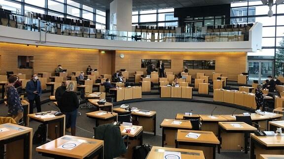 Blick in den Plenarsaal des Thüringer Landtages, in dem einige Abgeordnete sitzen und stehen.