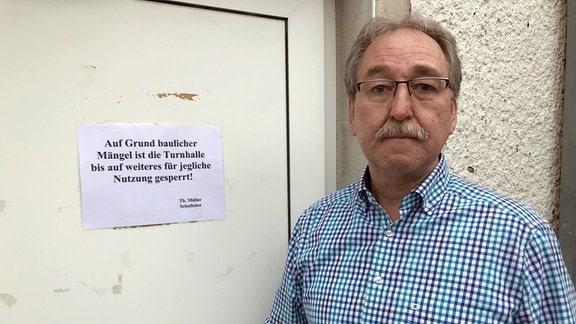 Schulleiter Thomas Müller steht vor einer verschlossenen Tür.