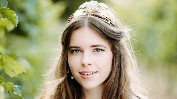 """Eine junge Frau steht zwischen Weinreben. Sie trägt ein Dirndel, eine Krone und eine Schärpe auf der """"Thüringer Weinprinzessin 2018-2019"""" steht. In den Händen hält sie ein Glas Wein"""