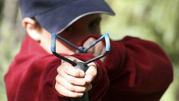 Ein Junge schießt mit einer Zwille.
