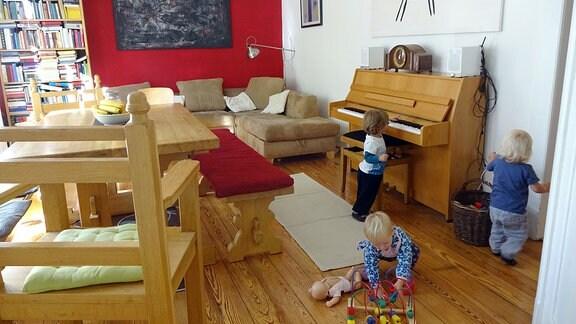 Drei Kinder spielen in einem großen Wohnzimmer mit Tisch, Sofa und Klavier.