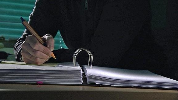 Eine Person im Halbdunkel notiert etwas in einem Aktenordner.
