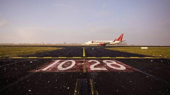 Markierung 10-28 und ein Flugzeug auf der Landebahn des Flughafen Erfurt-Weimar.
