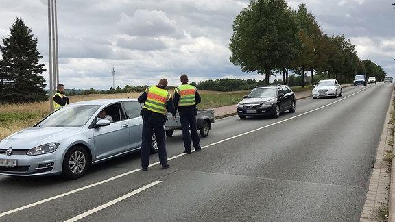 Polizisten kontrollieren ein Auto