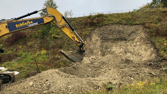 Ein Bagger gräbt mit seiner Schaufel an einer Felswand