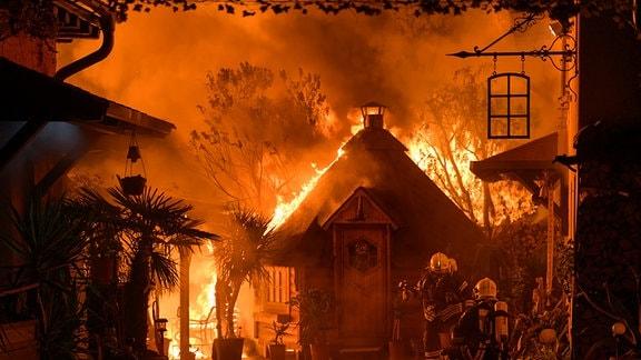 Eine Holzhütte brennt lichterloh