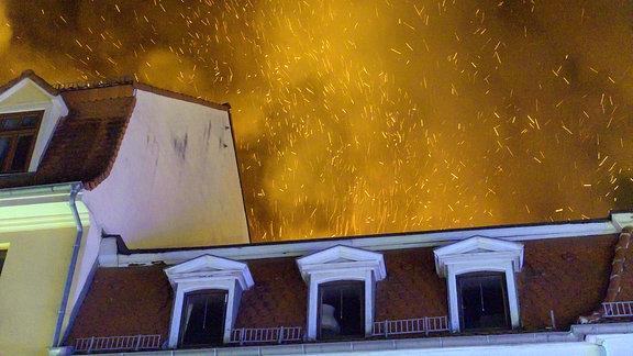 Über einem Hausdach sprühen Funken