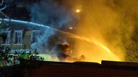 Ein dicker Wasserstrahl aus einem Feuerwehrschlauch strömt in ein Feuer