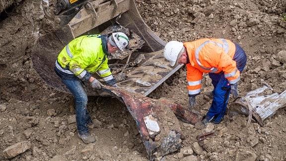 Zwei Männer ziehen ein Metallblech aus einer Baggerschaufel