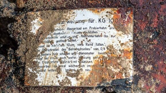 Verrostetes und teilweise lesbares Schild mit einer Gebrausanweisung für ein technisches Gerät