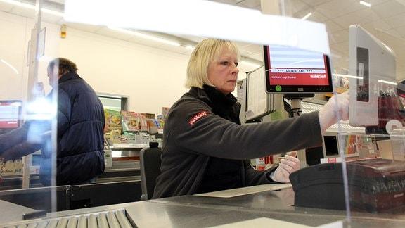 eine Verkäuferin in einem Supermarkt. Beim Regale einräumen, an der Kasse. Ein Mann mit Einkaufswagen nach dem Verlassen des SM. Die Wagen-Sammelstelle mit Schildern. Ein großes Nahkauf-Schild.
