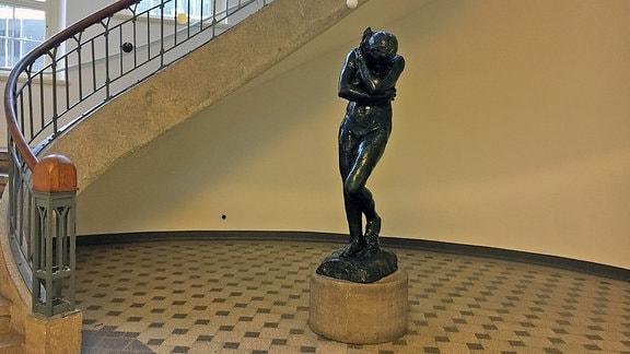 Skulptur einer Frau neben einem Treppenaufgang