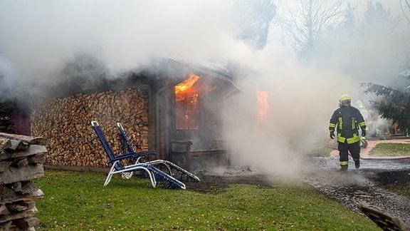 Qualm dringt aus einer brennenden Saunahütte.