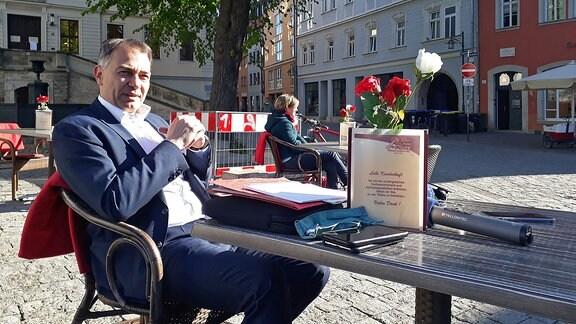Ein Mann sitzt vor einem Café an einem Tisch.
