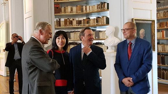 Drei Männer und eine Frau stehen in der Anna-Amalia-Bibliothek Weimar.