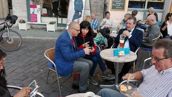 Eine Frau schaut in einem Straßencafé in Weimar auf das Handy eines anderen Mannes.