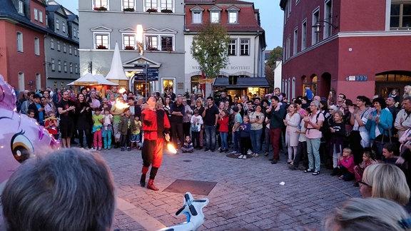 Ein Mann spielt mit Feuer auf einem Platz, Menschen schauen ihm zu.