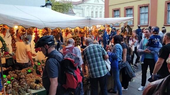 Menschen schauen sich an Marktständen die Waren an.