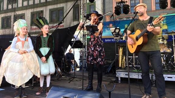 Zwei Musiker stehen zusammen mit zwei als Gemüse verkleideten Kindern auf der Bühne.