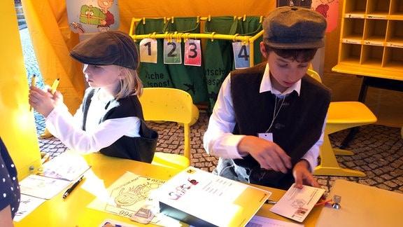 Zwei Kinder in einem nachgebildeten Postamt