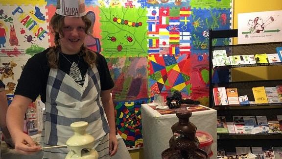 Ein Mädchen steht hinter zwei Schokoladenbrunnen.