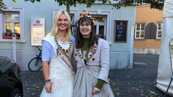 Zwei als Zwiebelköniginnen verkleidete Frauen halten sich in den Armen.