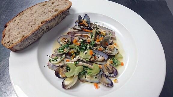 Verschiedene Muscheln in Spße auf einem Teller