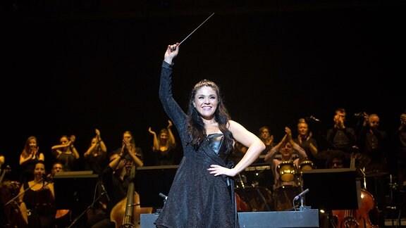 Wenn Sie den Taktstock hebt, kann es losgehen. Die Brasilianerin Alexandra Arrieche dirigiert das Antwerp Philharmonic Orchestra, das die Pop-Stars begleitet