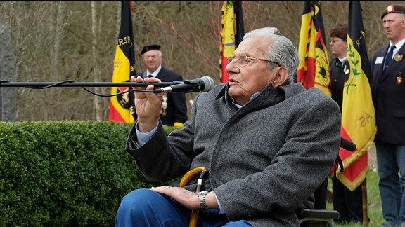 Älterer Mann in Rollstuhl spricht in Mikrofon. Im Hintergrund Uniformierte mit aufgestellten Fahnen