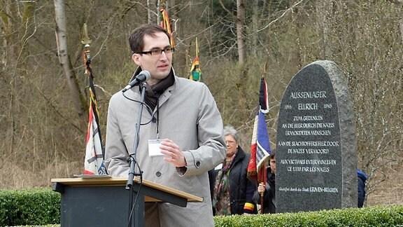 Mann in grauem Mantel an Pult mit Mikrofon. Im Hintergrund ein grauer Obelisk mit weißen Inschriften