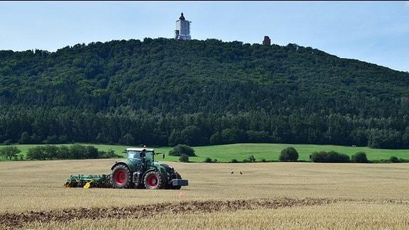 Ein Traktor auf einem Feld vor dem Kyffhäuser-Denkmal