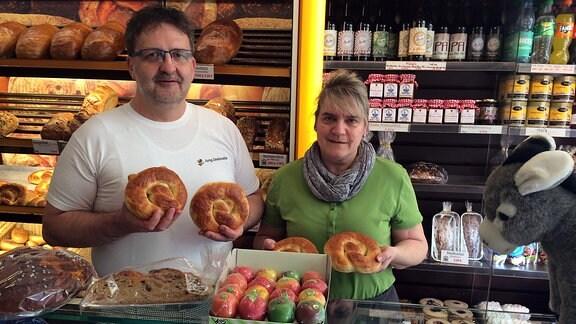 Ein Bäcker hält Brezeln in den Händen