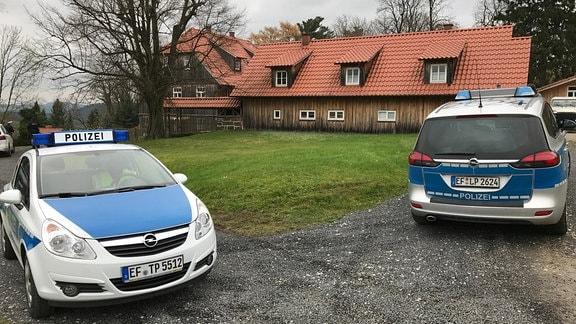 Zwei Polizeiautos stehen vor dem mit Holzbrettern verkleideten Wohnhaus des Thüringer AfD-Vorsitzenden Björn Höcke in Bornhagen im Eichsfeld