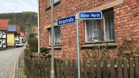 Ein Straßenschild steht vor einem Haus.