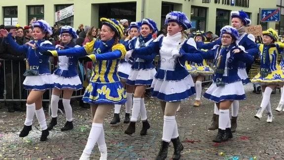 Mädchen in blau-weißen und balu-gelben Karnevalsuniformen tanzen auf Straße vor Zuschauern.