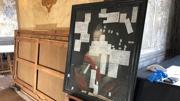 Ein historisches Gemälde mit Frau steht auf einer Staffelage und ist mit weißen Klebern beklebt