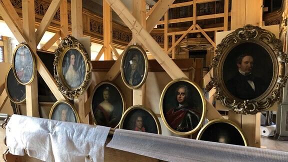 Einige alte Gemälde mit Männer und Frauenköpfen hängen an einem Holzgestellt, davor Packfolie