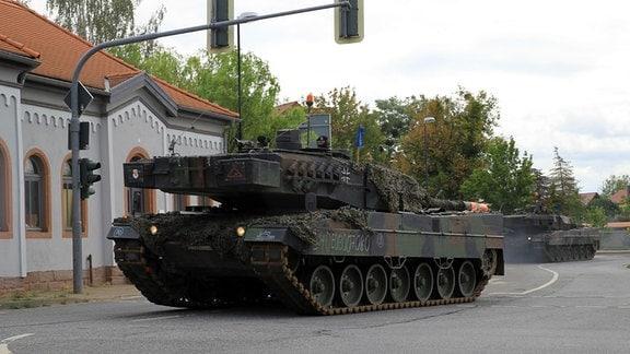 Zwei Bundeswehr-Panzer vom Typ Leopard 2 fahren über eine Kreuzung in Bad Frankenhausen.