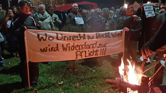 Vor einem Banner lodert ein Feuer.