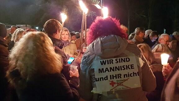 Mehrere Menschen bei einer Demo halten Fackeln in die Höhe.