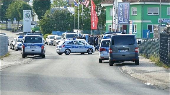 Auf einer Straße vor einem Autohaus stehen mehrere Polizeifahrzeuge und Personen