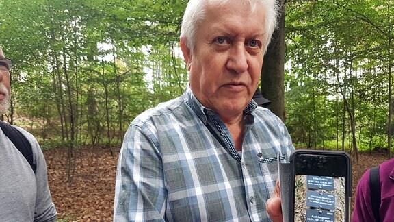 Ein Mann zeigt ein Foto auf einem Smartphone